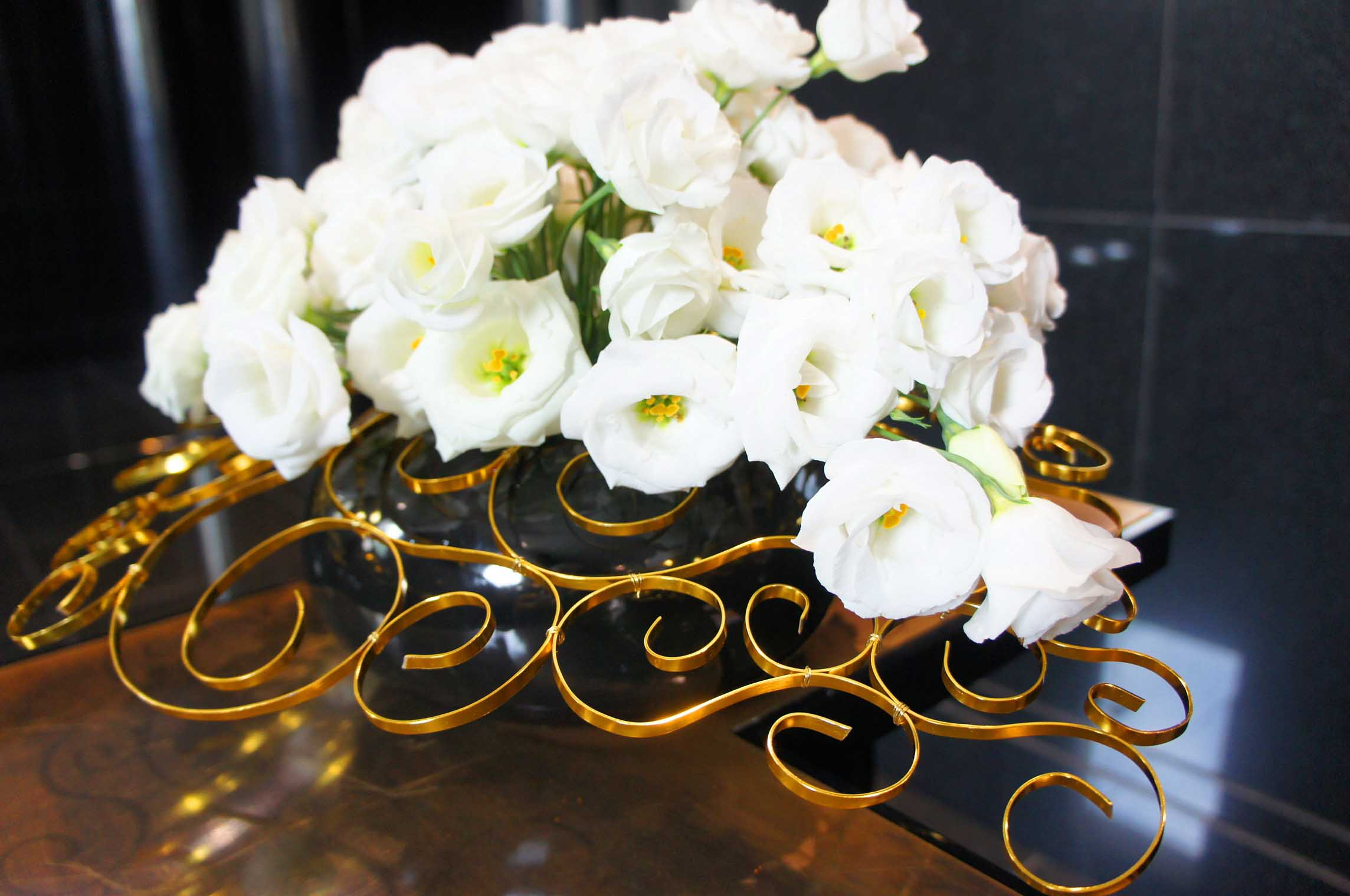 biała eustoma na wyplecionej z drutu konstrukcji jako dekoracja recepcji